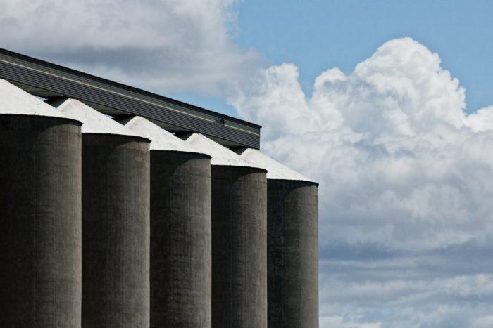 five grey grain silos in a row