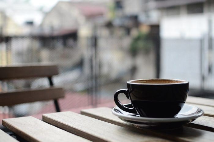 Cappuccino black cup on wood cafe table