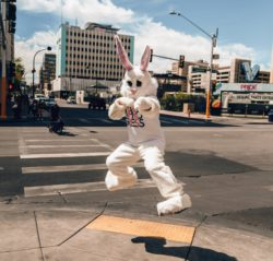 a person dancing in a white bunny suit downtown